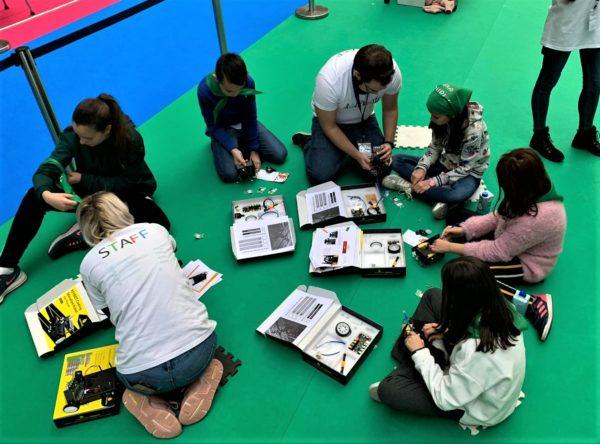 Monitores y niños trabajando con los kits de robótica educativa