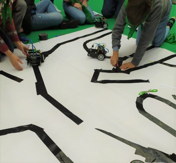Niños preparando una pista para que circulen coches autónomos de robótica